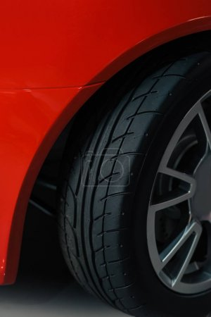 cropped shot of wheel of red sport car