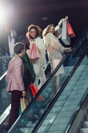 young stylish group of shoppers on escalator at shopping mall
