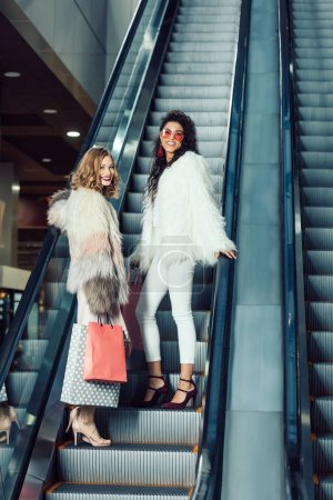 young women in fur coats riding escalator at shopping mall