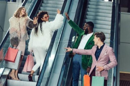 Photo pour Jeunes acheteurs masculins et féminins donnant cinq élevé sur les escaliers roulants au centre commercial - image libre de droit