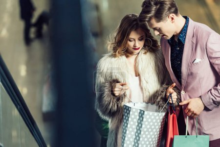 young stylish couple looking into shopping bags at mall