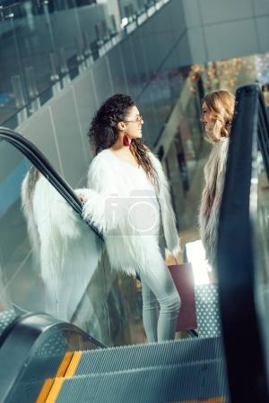 young women talking on escalator at shopping mall