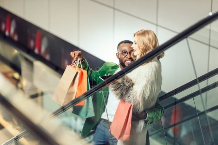 Photo for Happy young interracial couple talking while riding escalator at shopping mall - Royalty Free Image