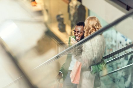 stylish young couple riding escalator and embracing at shopping mall