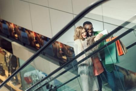 Photo pour Prise de jeune couple selfie alors qu'il circulait escalator au centre commercial - image libre de droit