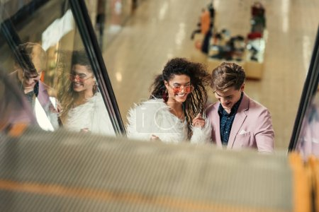 young couple riding escalator at shopping mall
