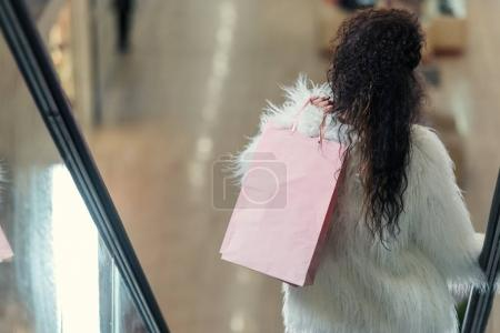 rear view of stylish woman holding shopping bag while riding escalator