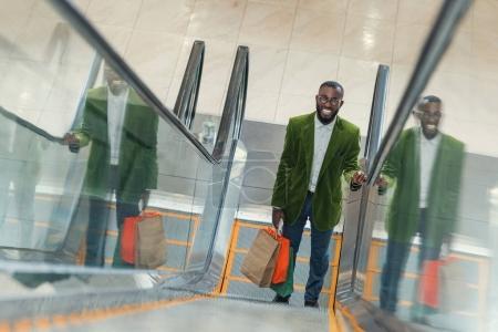 Photo pour Homme à la mode avec sac à provisions sur l'escalator au centre commercial souriant - image libre de droit