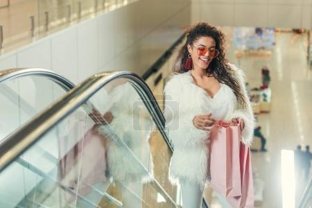 Photo pour Femmes élégantes heureux regardant dans le sac à provisions sur l'escalator au centre commercial - image libre de droit