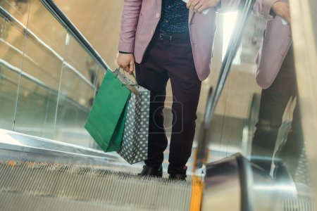 cropped shot of man with shopping bags on escalator
