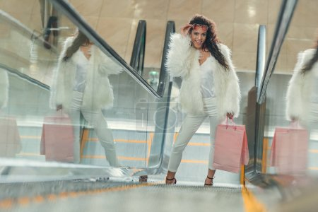 happy stylish young woman with shopping bags on escalator