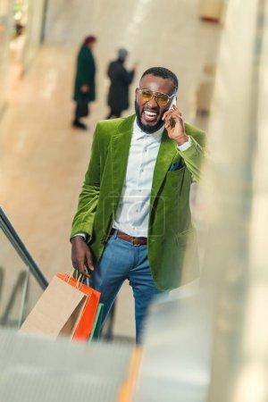 Photo pour Heureux homme élégant sur l'escalator au centre commercial et de parler par téléphone - image libre de droit