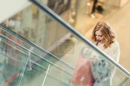 surprised woman with shopping bag riding escalator