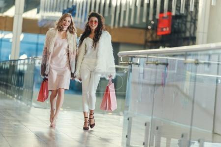 Photo pour À la mode jeunes femmes en manteaux de fourrure avec des sacs à provisions marche par mail - image libre de droit