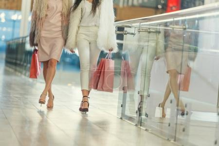 cropped shot of women in fur coats with shopping bags walking by mall