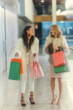 Photo pour Femmes élégantes en manteaux de fourrure avec des sacs à provisions marchant au centre commercial et riant - image libre de droit