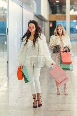 stylish women in fur coats with shopping bags walking by mall