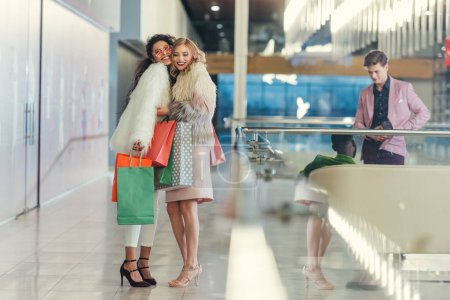 stylish women with paper bags meeting in shopping mall