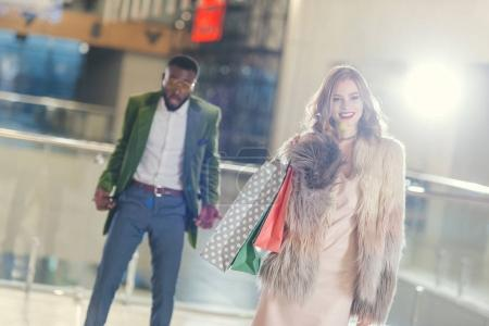 Photo pour Heureuse femme élégante avec des sacs à provisions éloigner choqué copain avec vides poches - image libre de droit