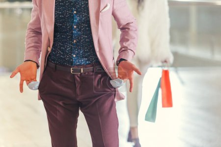 cropped shot of man showing empty pockets while girlfriend holding shopping bags and walking away blurred on background