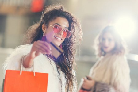 young stylish woman in fur coat with golden credit card on shopping