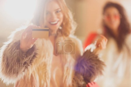 young woman in fur coat with golden credit card on shopping