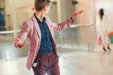stylish young man with empty pockets turning back on girlfriend while she walking away at shopping mall
