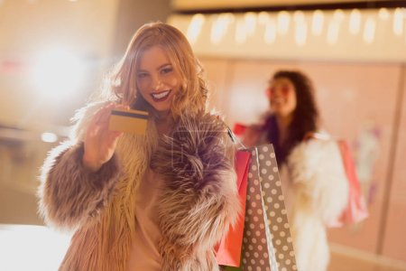 smiling young woman in fur coat with golden credit card on shopping