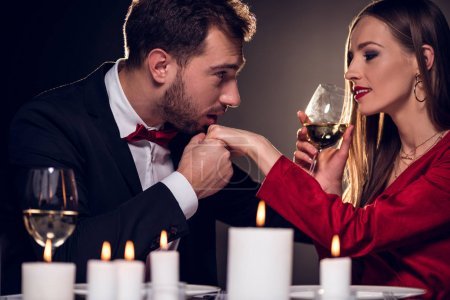 woman drinking wine while man kissing her hand on romantic date in restaurant