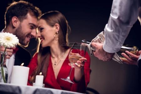Photo pour Serveur verser du vin tout en souriant couple ayant rendez-vous romantique au restaurant le jour de la Saint-Valentin - image libre de droit