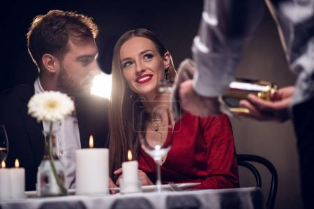 Photo for Waiter pouring wine while happy couple having romantic date in restaurant on valentines day - Royalty Free Image