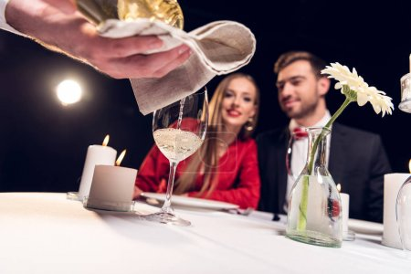 Photo for Selective focus of waiter pouring wine while couple having romantic date in restaurant - Royalty Free Image