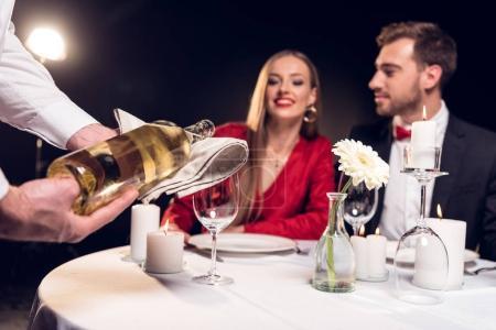 Photo pour Garçon, verser le vin tout en couple ayant rendez-vous romantique au restaurant le jour de la Saint-Valentin - image libre de droit