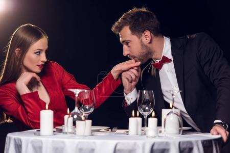 man kissing hand of his girlfriend on romantic date in restaurant