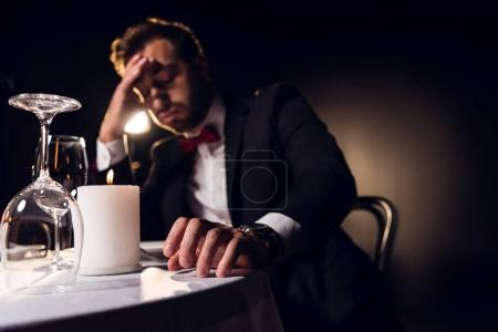 handsome upset man waiting for romantic date in restaurant
