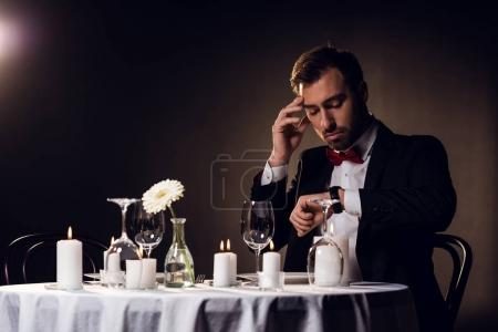 worried man looking at watch while waiting for romantic date in restaurant