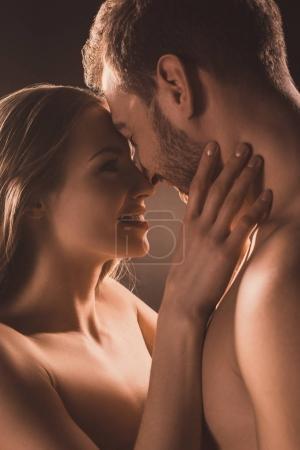 Photo pour Heureux amateurs nus souriant et embrassant, sur brun - image libre de droit