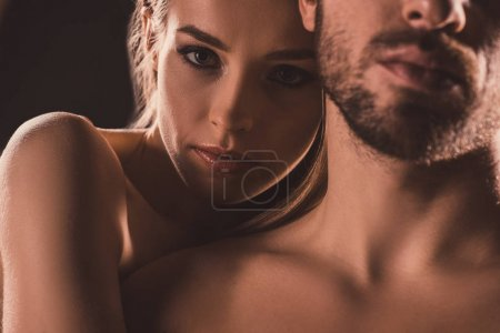 sensual lovers embracing and looking at camera, on brown