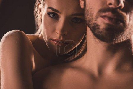Photo pour Amoureux sensuels embrasser et regarder la caméra, sur brun - image libre de droit