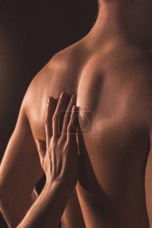 Photo pour Vue recadrée de la femme touchant le dos de son amant, isolée sur brun - image libre de droit