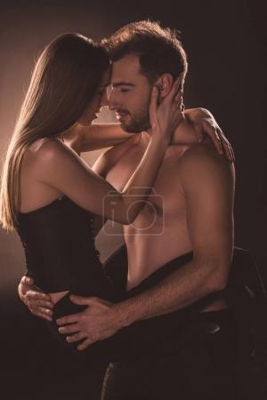 passionate lovers embracing and looking at each other, on brown