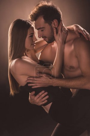 seductive couple embracing and looking at each other, on brown