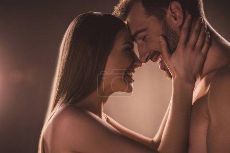 Photo pour Amoureux sensuels embrassant et riant, sur brun - image libre de droit