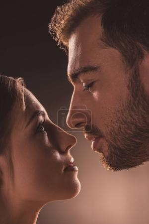 passionate couple looking at each other, on brown