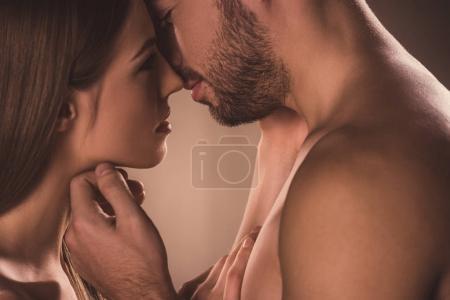 Photo pour Couple sensuel embrasser et regarder l'autre, sur brun - image libre de droit