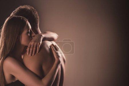 Photo pour Couple nu sensuel embrassant les yeux fermés, sur brun - image libre de droit