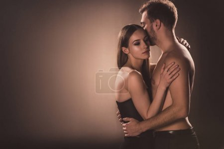 sensual nude lovers embracing, on brown with copy space