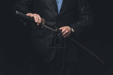 cropped shot of man in suit taking out his katana sword isolated on black