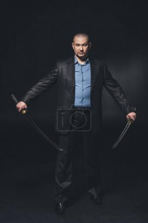 handsome serious man in suit with dual katana swords on black