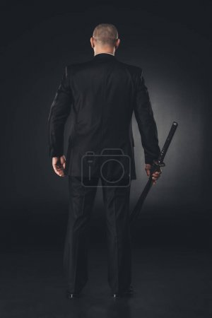 rear view of man in suit with katana sword on black
